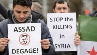 Gegner des syrischen Regimes von Präsident Baschar al-Assad protestieren in Genf.