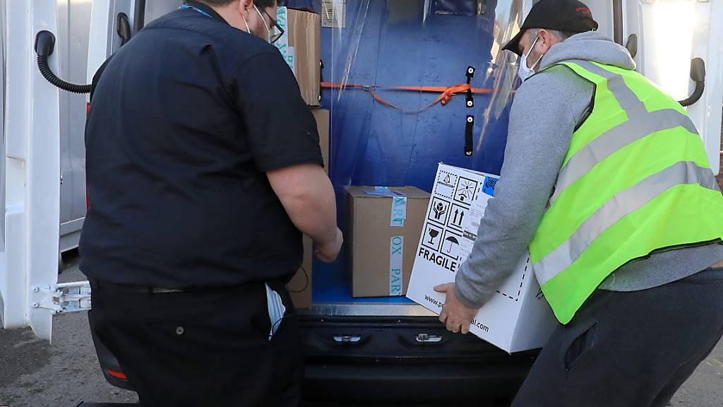 Ein Apothekentechniker des Gesundheitsdienstes von Croydon (l) nimmt im Universitätskrankenhaus Croydon die erste Charge der Covid-19-Impfungen entgegen, die in das Gebiet geliefert werden sollen. Foto: Gareth Fuller/PA Wire/dpa