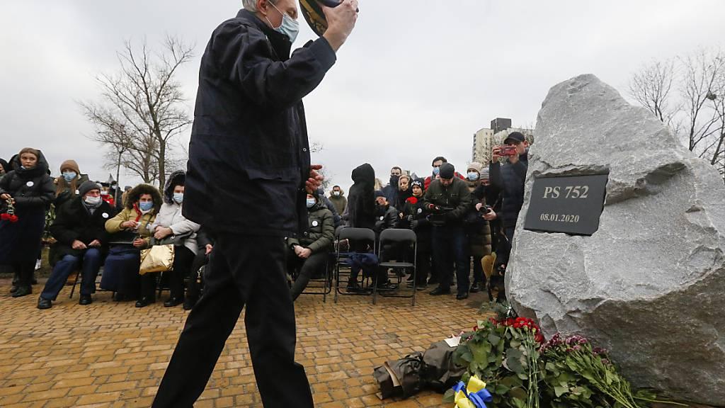 Ein Pilot legt Blumen vor der Gedenkstätte für die Opfer des Absturzes einer ukrainischen Passagiermaschine nieder. Ein Jahr nach dem Abschuss des Flugzeuges dringt Präsident Selenskyj auf den Beginn eines Gerichtsverfahrens. Foto: Efrem Lukatsky/AP/dpa