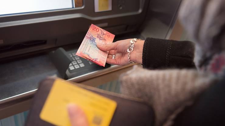 Immer mehr Schweizer bezahlen mit dem Kärtchen statt mit Bargeld: eine Frau hebt 20 Franken ab (Symbolbild).