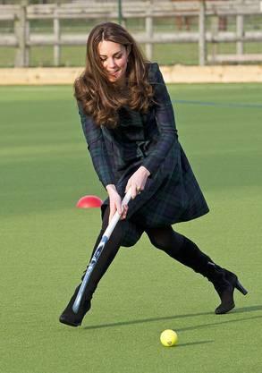 Sportliche Kate schwingt den Landhockey-Stock bei einem Besuch der St. Andrew School.