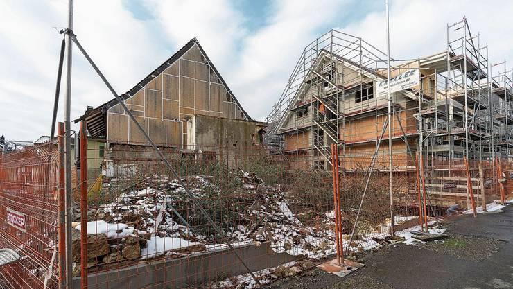 Seit dem Baustopp schützt eine provisorische Bretterwand den noch bestehenden Teil des Murihofs. Daneben die Neubauten.