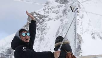 Ein asiatischer Tourist macht ein Selfie auf dem Jungfraujoch.