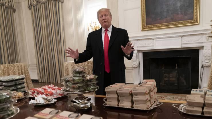Pizza, Hamburger und Pommes anstelle feiner Häppchen: Wegen der Haushaltssperre hat US-Präsident Donald Trump ein Hochschul-Football-Team im Weissen Haus mit Fastfood bewirtet.