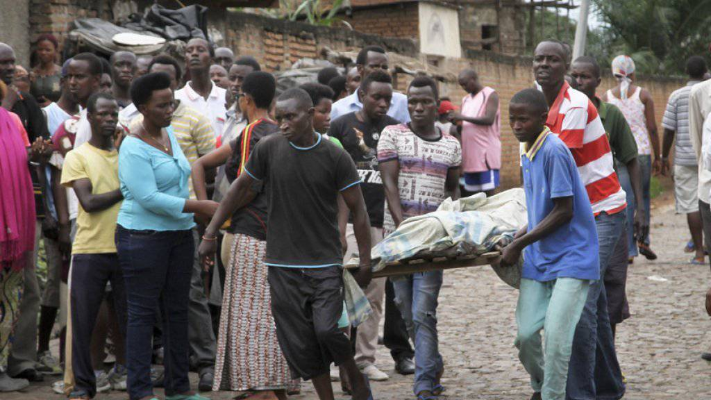 Einwohner der Hauptstadt Bujumbura tragen am Samstag eine Leiche weg.