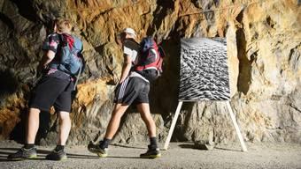 Carlier hat seine Fotografien in einem nur schwach beleuchteten Stollen installiert, wo der Wanderer den Boden und die vielen Pfützen nur schwer erkennen kann.