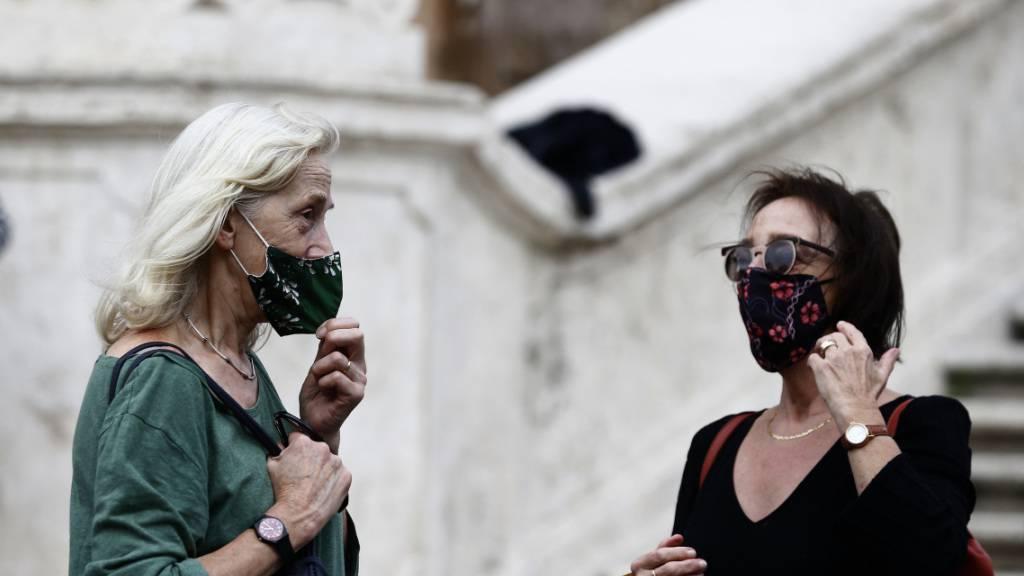 ARCHIV - Menschen mit Mund-Nasen-Schutz stehen vor einer Treppe in Rom. Angesichts landesweit steigender Zahlen von Corona-Neuinfektion führt Italien eine Maskenpflicht im Freien ein. Foto: Cecilia Fabiano/LaPresse via ZUMA Press/dpa