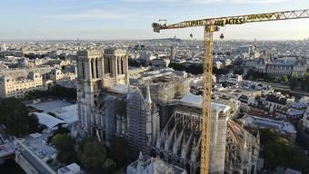 """HANDOUT - Ein Transparent: """"Klima. In Aktion"""" ist an einem Kran an der Baustelle der Kathedrale Notre Dame befestigt. Mit einer Aktion auf der Baustelle der Kathedrale Notre-Dame hat die Umweltschutzorganisation Greenpeace in Paris für Aufsehen gesorgt. Foto: Uncredited/Greenpeace/AP/dpa - ACHTUNG: Nur zur redaktionellen Verwendung und nur mit vollständiger Nennung des vorstehenden Credits"""