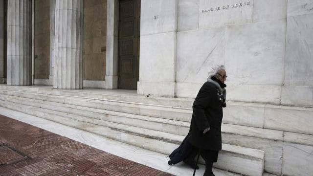 Ältere Frau unterwegs vor dem Hauptsitz der Bank of Greece in Athen
