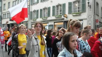 Der Chor Canto aus Polen kommt mit dem befreundeten Bez-Chor Brugg auf der Hauptstrasse die Altstadt hinunter.