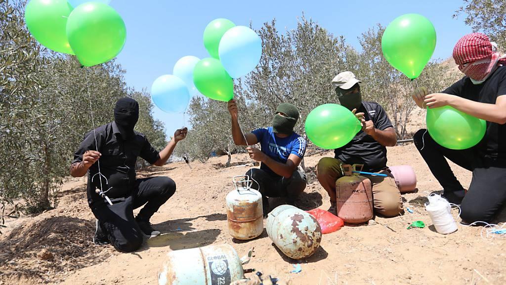 Maskierte Palästinenser bereiten in der Nähe des Lagers Al-Bureij im Zentrum des Gazastreifens Brandballons vor (24.08.2021). Nach Angriffen militanter Palästinenser im Gazastreifen mit Brandballons hat Israels Luftwaffe erneut Ziele in dem Palästinensergebiet beschossen. Foto: Ashraf Amra/APA Images via ZUMA Press Wire/dpa