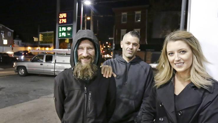 Der Obdachlose Johnny Bobbitt (l.) mit Kate McClure und deren Freund Mark D'Amico bei einer Tankstelle in Philadelphia, wo Johnny Benzin für Kate kaufte.