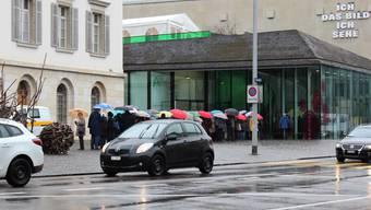 """Vor dem Kunsthaus stehen die Leute im strömenden Regen Schlange, um die Ausstellung """"Blumen für die Kunst"""" zu sehen."""