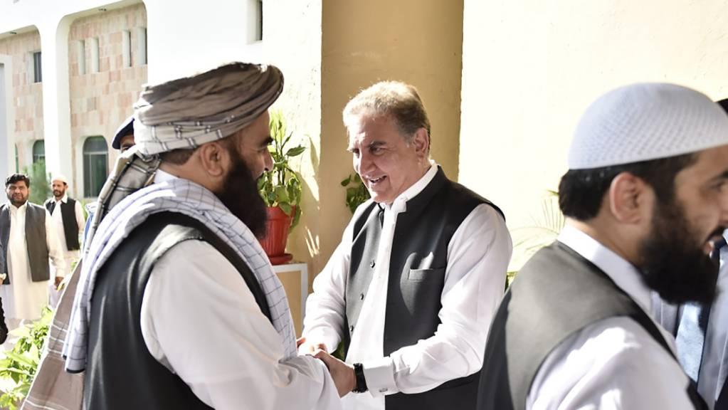 Händeschütteln und Umarmungen für die Taliban: Pakistans Aussenminister Shah Mehmood Qureshi (Mitte) beim Begrüssen der Delegation in Islamabad.