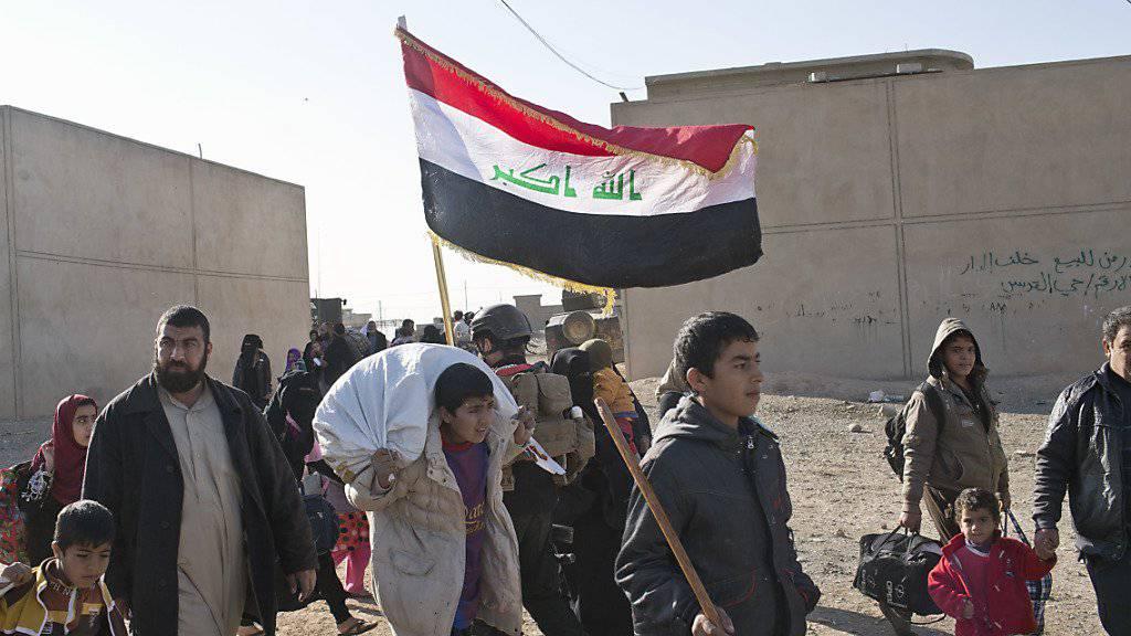 Bei Kämpfen vertriebene Menschen kehren unter einer irakischen Flagge zurück nach Gogdschali bei Mossul