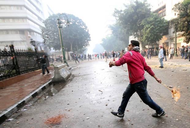 Ein Demonstrant wirft eine Brand-Bombe.