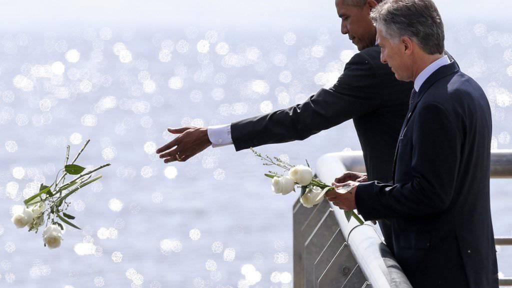 US-Präsident Obama und sein argentinischer Amtskollege Macri werfen an der Gedenkstätte für die Opfer der argentinischen Militärdiktatur Blumen in den Fluss.