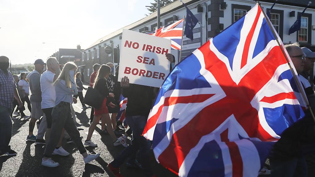 Demonstranten halten britische Fahnen und ein Schild mit der Aufschrift «No Irish Sea Border» bei einem Protest protestantischer Loyalisten gegen das sogenannte Nordirland-Protokoll.