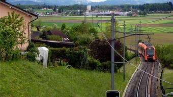 Ein RBS-Zug unterwegs in Richtung Bätterkinden und in Richtung jenes Feldes im Stockacher (hinten links), demmöglichen Standort für ein Depot.