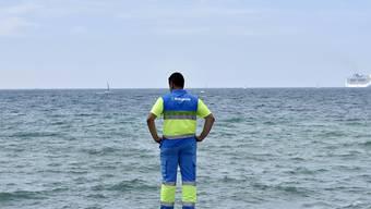 Können einem den Badespass schnell einmal verderben: Ein Helfer hält am Strand El Molinar in Palma des Mallorca Ausschau nach Portugiesischen Galeeren.
