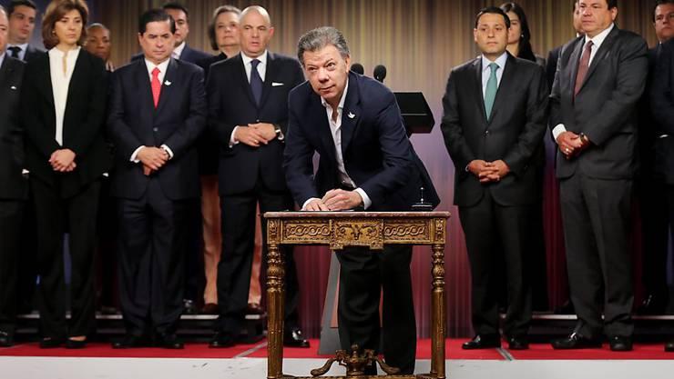 Kolumbiens Präsident Juan Manuel Santos unterschreibt den Antrag für ein Referendum über ein Friedensabkommen mit der FARC. (Archivbild)