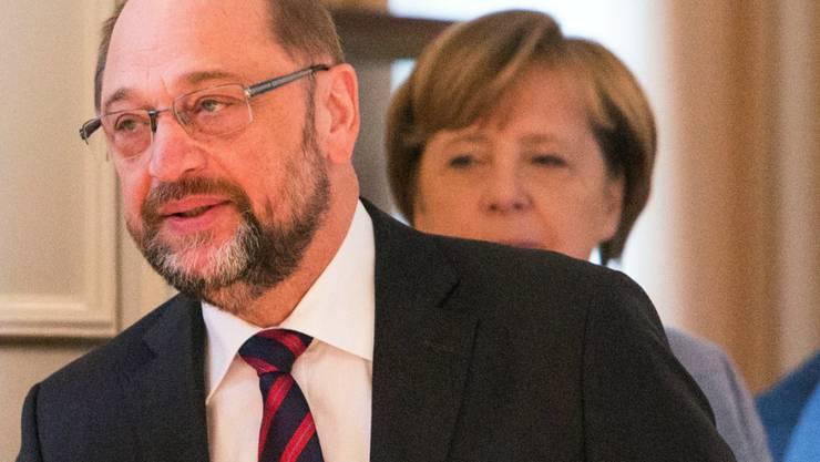 Wer geht als Sieger aus den Koalitionsverhandlungen in Berlin? SPD-Chef Schulz darf vor allem die Jusos nicht enttäuschen, sonst segnen die die Ergebnisse der Verhandlungen mit der Union zur Bildung einer neuen deutschen Regierung nicht ab. Im Hintergrund Bundeskanzlerin und CDU-Parteichefin Merkel.