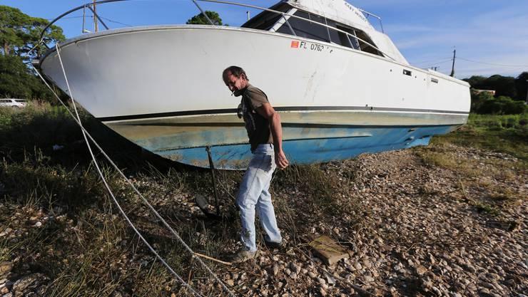 Der nun zum Sturm herabgestufte Hurrikan Hermine sorgt in Florida für viel Aufregung. Hier begutachtet ein Mann in East Point sein Boot, das an Land gespült wurde.