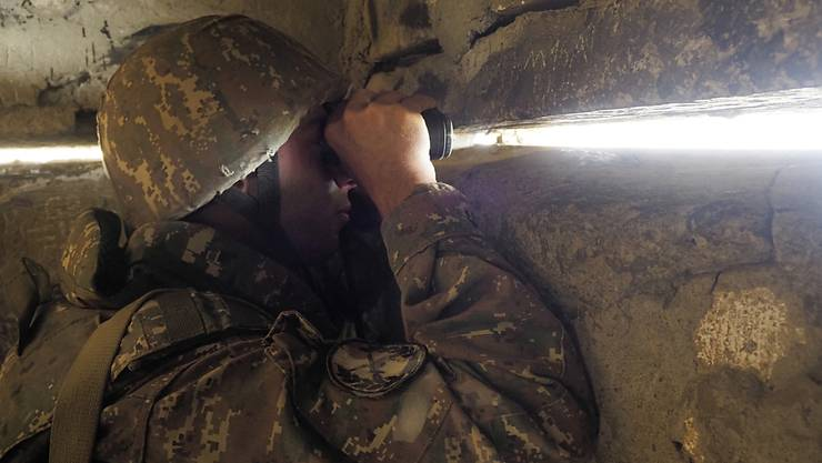 dpatopbilder - Ein armenischer Soldat blickt in einem Unterschlupf an der Front in Richtung der aserbaidschanischen Stellungen. Foto: -/AP/dpa