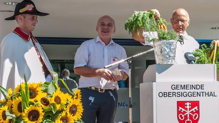 Zum Dank erhält Bundespräsident Ueli Maurer (Mitte) von Gemeindeammann Max Läng einen Korb Rüebli. PHN