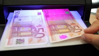 Ein Mitarbeiter der deutschen Bundesbank prüft unter einem UV-Lichtgerät einen falschen (links) und einen echten 50-Euro-Schein. Noch nie wurden so viele Euro-Blüten aus dem Verkehr gezogen wie 2015. (Archiv)