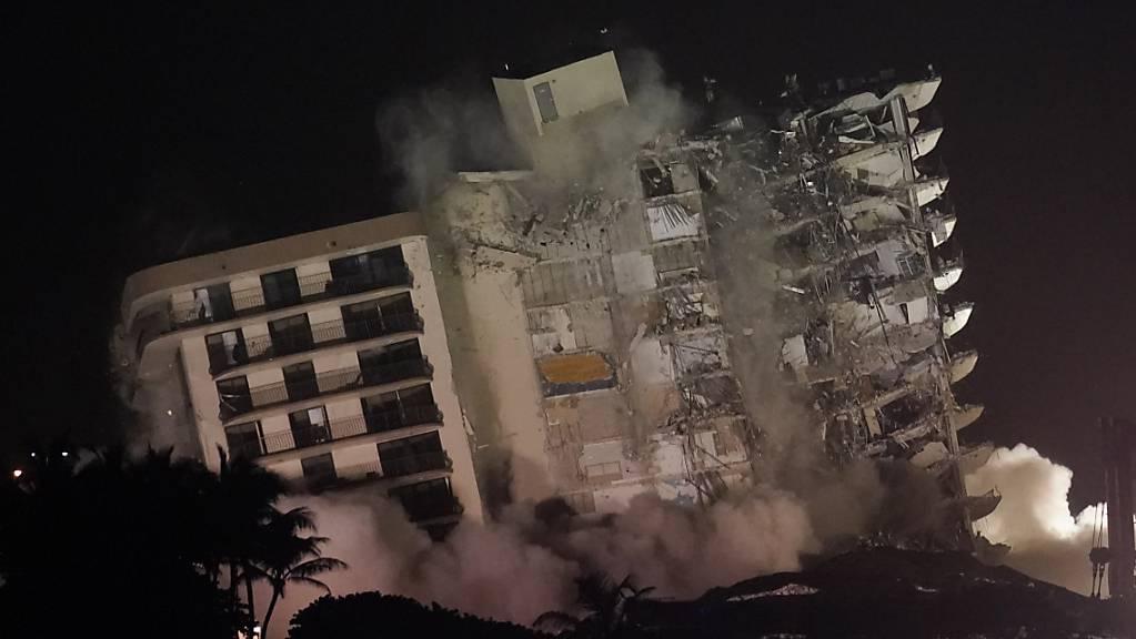 Die beschädigte Reststruktur des Champlain Towers South Condo Gebäudes stürzt ein. Nach dem Teileinsturz des Wohnkomplexes in der Nähe von Miami ist der noch stehende Gebäudeteil gesprengt werden. Die Ruine war instabil. Foto: Lynne Sladky/AP/dpa Foto: Lynne Sladky/AP/dpa