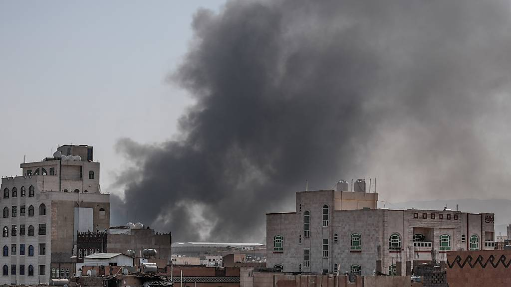 Schwarzer Rauch steigt zwischen Gebäuden auf. Das von Saudi-Arabien angeführte Bündnis startet mehrere Luftangriffe auf die von Houthi-Rebellen besetzten Stadt. Dabei sollen mindestens 120 Kämpfer der Huthi-Rebellen getötet worden sein. Foto: Hani Al-Ansi/dpa