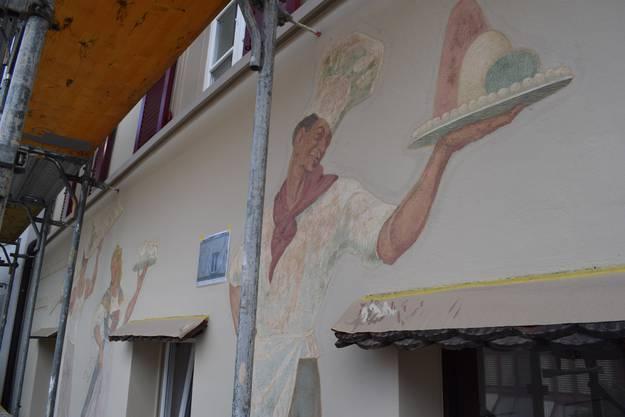Auch Cafebetreiber Felix Mühleisen lässt seine Fassade restaurieren. Abgebildet sind eine Serviceangestellte und zwei Bäcker.