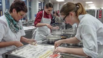 Kochkunst auf beachtlichem Niveau: Maya Reber (Mitte), Absolventin der Koch-Ausbildung, mit Helferinnen bei der Menü-Zubereitung in der Murianer Spitalküche. chr