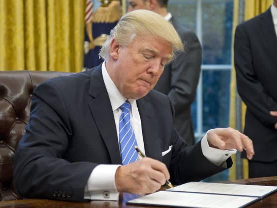 Mit dem Kugelschreiber die TPP-Teilnahme beerdigt: Trotz Trumps Rückzug der USA aus dem Handelsabkommen soll TPP weiterleben.