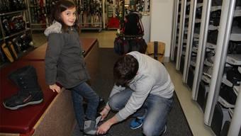 Die 8-jährige Talma wird beim Probieren der Snowboard-Schuhe von Silvan Baer betreut.