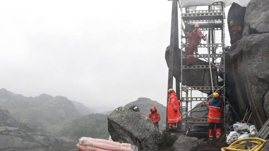 Handwerker versuchen, mit Eisenkeilen, Spezialleim und Zement den «Trollpenis» zu befestigen.