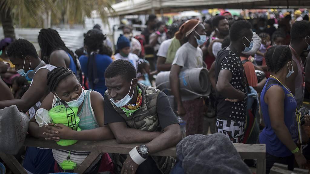 ARCHIV - Haitianische Migranten warten darauf, an Bord eines Boots in Richtung Capurgana nahe der Grenze zu Panama zu gehen. Foto: Ivan Valencia/AP/dpa