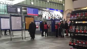 Personal mit roten SBB-Westen in der Schalterhalle.