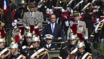 Frankreichs Präsident François Hollande im offenen Fahrzeug während der Militärparade zum Nationalfeiertag im Zentrum von Paris