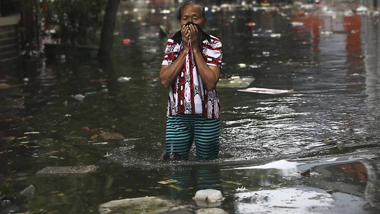 Eine Frau watet am Samstag durch das Wasser in Jakarta, Indonesien. Nach den schweren Überschwemmungen ist die Zahl der Toten auf mindestens 53 gestiegen.