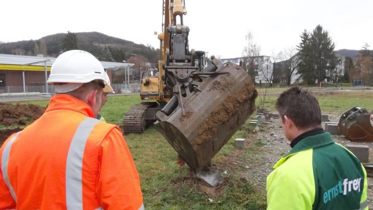 Mit der Baggerschaufel wird ein auf dem Bauplatz vorhandener Betonpfeiler herausgelöst