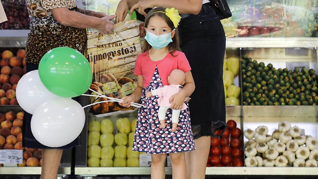 Ein Mädchen mit medizinischem Mundschutz hält Luftballons und eine Puppe in einem Lebensmittelmarkt in Bukarest. Rumänien verzeichnet einen Rekord an Neuinfektionen mit dem Coronavirus.