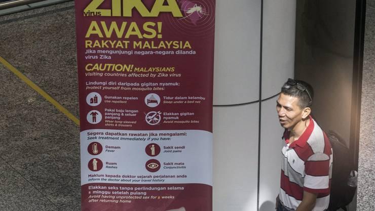 Ein Plakat informiert am Flughafen von Kuala Lumpur Reisende über das Zika-Virus. (Archiv)