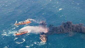 Löschboote bei der Arbeit im brennenden Öltanker. (Archiv)