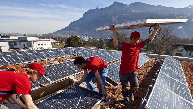 Die Ausgaben für erneuerbare Energie bleiben grösstenteils in der Schweiz: Handwerker installieren auf dem Dach der neuen Turnhalle in Sevelen SG eine Solaranlage. Key