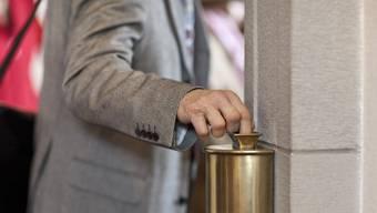 Ein Dieb wird beobachtet, wie er versucht, Geld aus einem Opferstock zu fischen. (Symbolbild)