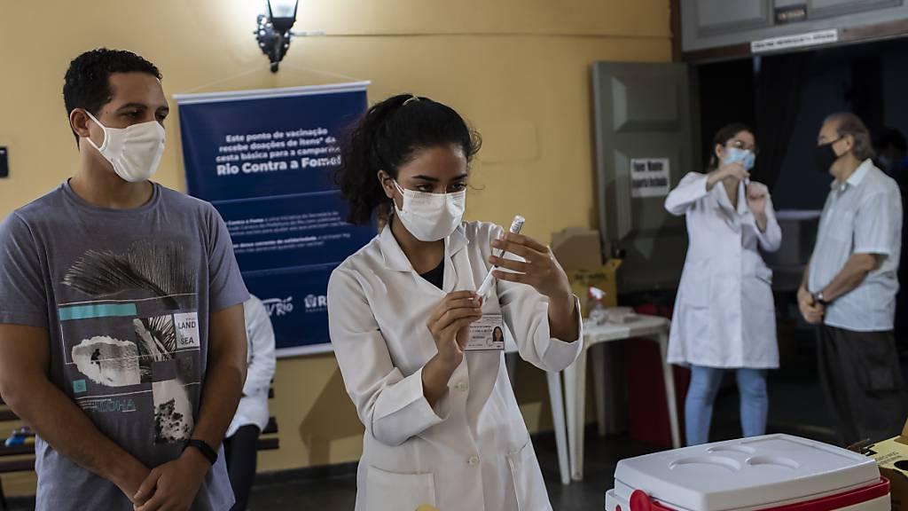 Eine Gesundheitsarbeiterin bereitet eine Spritze mit einem Corona-Impfstoff vor. Angesichts der verharmlosenden Politik der Regierung von Präsident Bolsonaro in Bezug auf die Pandemie sind tausende Brasilianer auf die Straße gegangen. Foto: Bruna Prado/AP/dpa