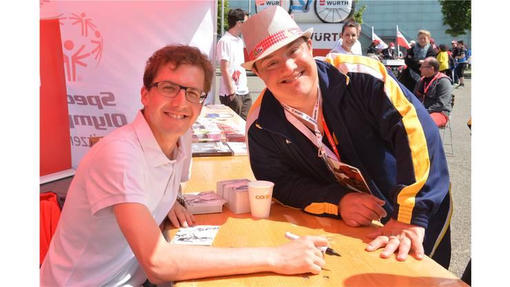 Skisprung-Olympiasieger Simon Ammann (links) verteilt sichtlich begeistert Autogramme.