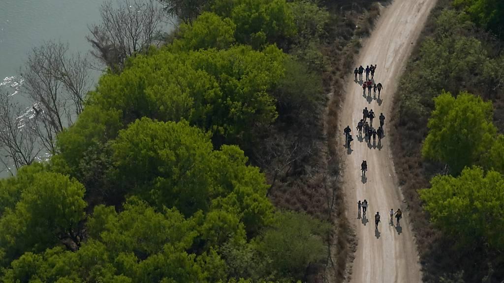 ARCHIV - Migranten gehen einen Feldweg entlang, nachdem sie die Grenze zwischen Mexiko und den USA überquert haben. Foto: Julio Cortez/AP/dpa